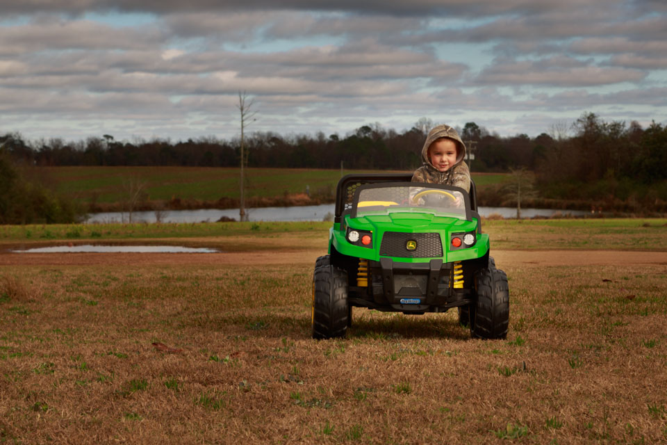 A tree year old boy in camouflage driving a John Deere toy truck