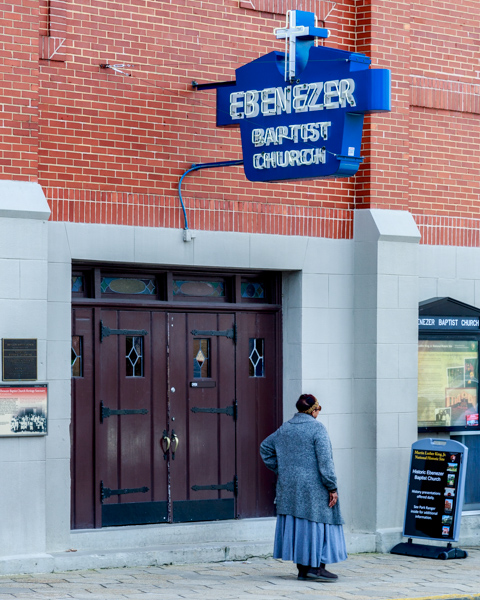 A grandmother poses for her picture in front of historic Ebenezer Baptist.